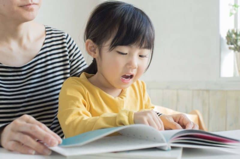 Young asian girl reads pointing a finger as she follows the words in a book